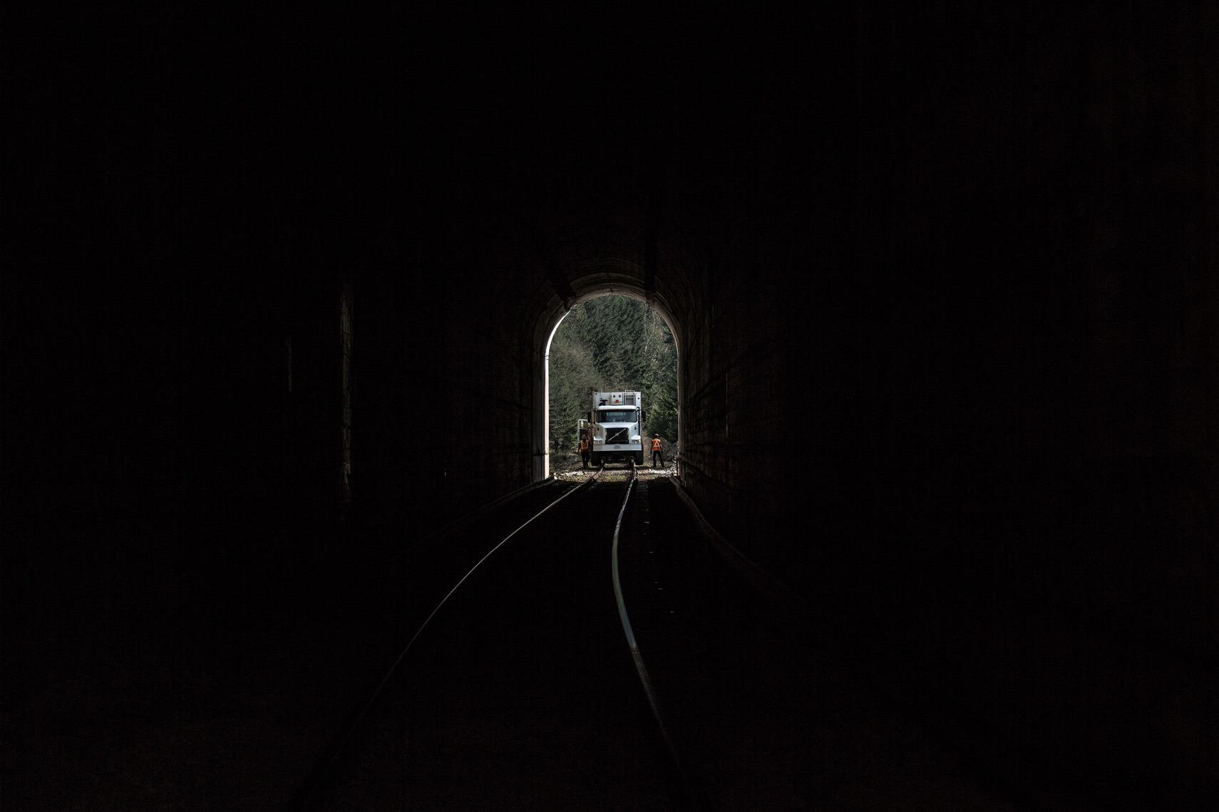 railroad workers working at the end of a tunnel